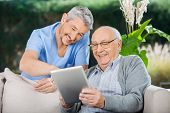 image of nursing  - Happy male caretaker and senior man using tablet PC at nursing home porch - JPG