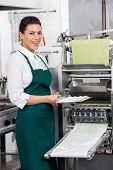 Portrait of happy female chef holding ravioli pasta tray by machine at commercial kitchen