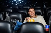 Relaxed happy man watching movie in cinema theater