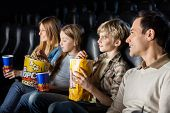 Family having snacks while watching movie in cinema theater