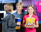 Portrait of happy girl holding popcorn while brothers talking at cinema
