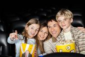 Happy girl showing something to family while watching movie in cinema theater