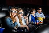 Portrait of happy woman watching 3D movie with family in cinema theater