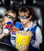 Portrait of happy sisters having snacks while watching 3D movie in cinema theater