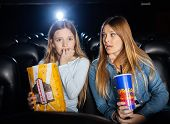 Woman looking at scared daughter watching movie in cinema theater