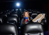 Woman with feetup on seat drinking cola while watching movie at cinema theater