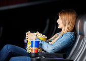 Side view of smiling woman holding snacks while watching movie at cinema theater