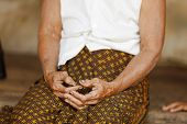 Close up on the wrinkled hands of an aged Cambodian woman farmer