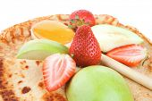 dessert : thin round pancake with honey strawberries and apple isolated over white background