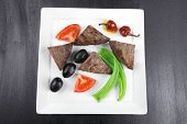 meat food : roast beef fillet mignon served on white plate with apples dill and tomatoes over black wooden table