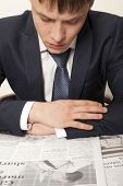 Business man reading a newspaper, gray backgrounds