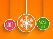 Christmas sale poster with colorful hanging X-mas balls decorated with stylish text and snowflake on orange background.