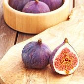 Fresh figs in plate on rustic vintage wooden table