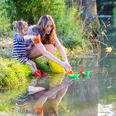 picture of little kids  - Young beautiful woman and her little daughter playing together with paper boats in a river - JPG