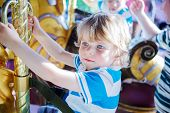 Little Cute Boy During Carousel Ride, Enjoying And Having Fun