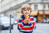 Little Cute Child On A Street Of City Eating Fresh Croissant
