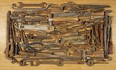 Various Old And Rusty Tools, Spread Out On A Wooden Table.