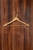 Closeup of an empty wooden hanger hanging from a hook on a dark wood paneled wall. Vertical format.