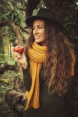 winter autumn girl in wood with apple in hand stand by tree wearing hat, wool scarf and green dress