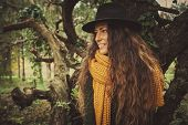 young smiling woman wearing hat, yellow wool csarf and green dress  in park  autumn winter fashion