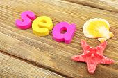 Sea word formed with colorful letters on wooden background