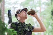 war, hiking, army and people concept - young soldier or ranger with gun drinking from flask in forest