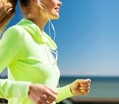 sport and healthy lifestyle concept - woman running and listening music with earphones outdoors