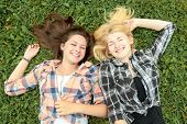 Blonde and brunette girl lying on grass