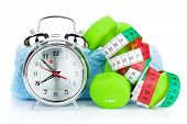 Two green dumbells, tape measure and alarm clock. Fitness and health. Isolated on white background