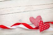 Valentines day background with toy hearts and ribbons over white wooden table background