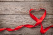 Valentines day heart shaped red ribbon over wooden table background with copy space