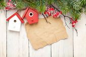 Christmas wooden background with fir tree and birdhouse decor. View from above with paper for copy space