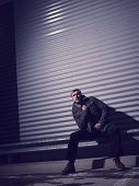 picture of overcoats  - Fashionable young man wearing a warm overcoat corrugated iron wall on background  - JPG