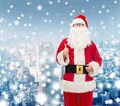 christmas, holidays, gesture and people concept- man in costume of santa claus showing thumbs up over snowy city background
