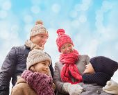 family, childhood, season and people concept - happy family in winter clothes over blue lights background