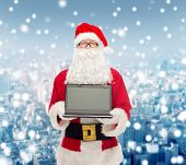 christmas, advertisement, technology, and people concept - man in costume of santa claus with laptop computer over snowy city background