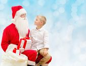 holidays, christmas, childhood and people concept - smiling little boy with santa claus and gifts over blue lights background