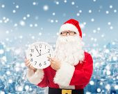 christmas, holidays and people concept - man in costume of santa claus with clock showing twelve pointing finger over snowy city background