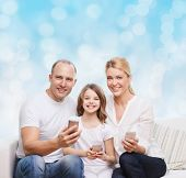 family, holidays, technology and people concept - smiling mother, father and little girl with smartphones over blue lights background