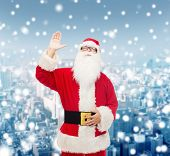 christmas, holidays, gesture and people concept - man in costume of santa claus waving hand over snowy city background