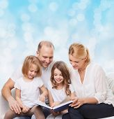 family, childhood, holidays and people - smiling mother, father and little girls reading book over blue lights background