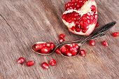 Juicy ripe pomegranates seeds in spoons, on old wooden table
