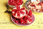 Beautiful composition with juicy  pomegranate seeds, on yellow wooden table