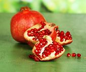 Juicy ripe pomegranates on green wooden table