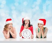 christmas, winter, holidays, time and people concept - smiling women in santa helper hats with clock over blue lights background