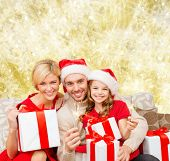 christmas, holidays, family and people concept - happy mother, father and little girl in santa helper hats with gift boxes and sparklers over yellow lights background