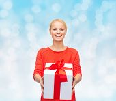 christmas, holidays, valentine's day, celebration and people concept - smiling woman in red clothes with gift box over blue lights background