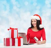 christmas, shopping and people concept - smiling woman in santa helper hat with gift boxes, laptop computer and credit card over blue lights background