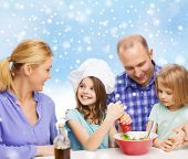 food, family, children, happiness and people concept - happy family with two kids making salad for dinner over blue sky and snowflakes background