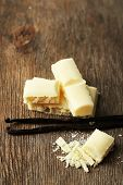 Tasty white porous chocolate with vanilla sticks on wooden table, close up